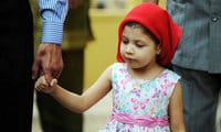 A young Indian Zoroastrian or Parsi girl holds her father\'s hand as they arrive at a fire temple to offer prayers