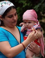 An Indian Zoroastrian or Parsi woman gives a sweet to a child  in Mumbai in August